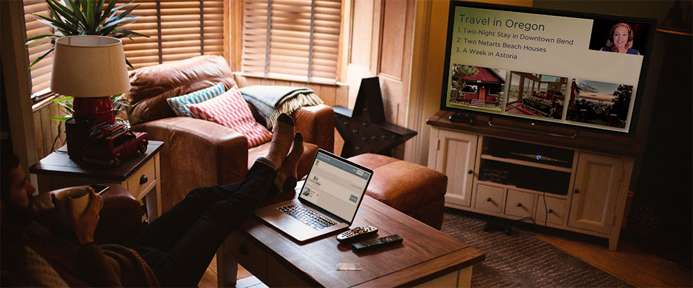 a living room with a person watching a live auction on a tv and using a latptop to bid on auction items