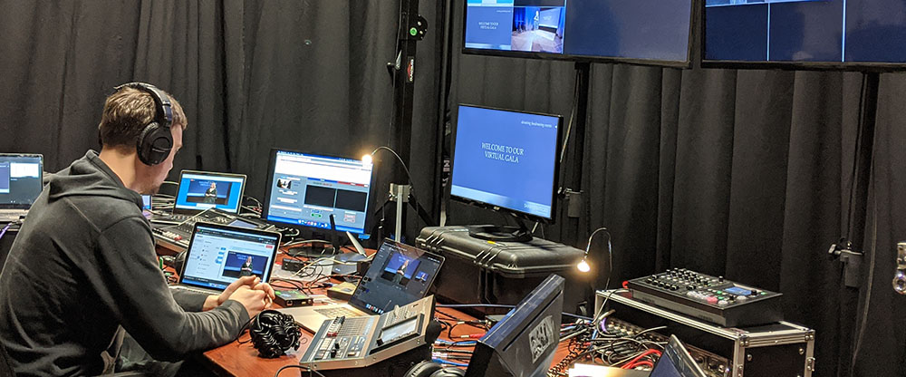 audiovisual technician sits at a tech table while monitoring multiple monitors and laptops