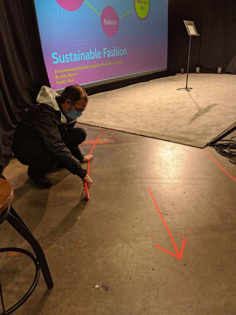 a person tapes directional marks on a floor