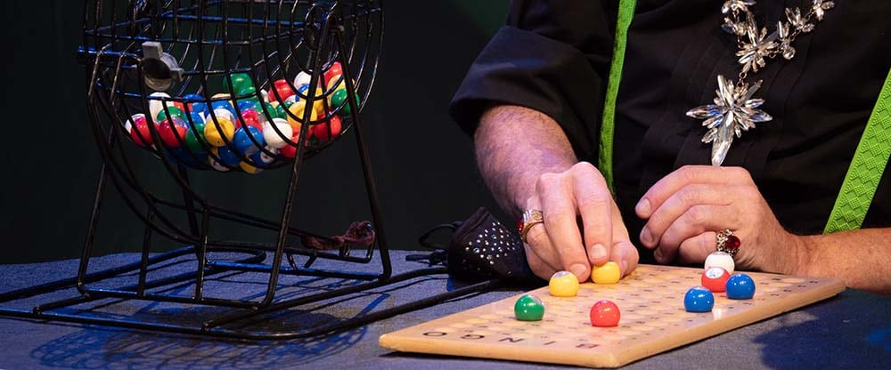 a person calls numbers for a Bingo game and places the numbers on a wooden Bingo board