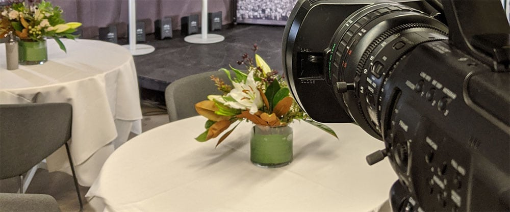 Tables set with flowers and table clothes are in front of a stage. A video camera is pointed to the stage.
