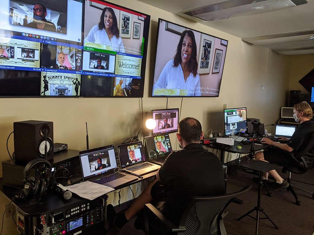 multiple inputs for a livesteam are seen on large monitiors mounted on a wall while a livestream director sits at a table with laptops and switchers