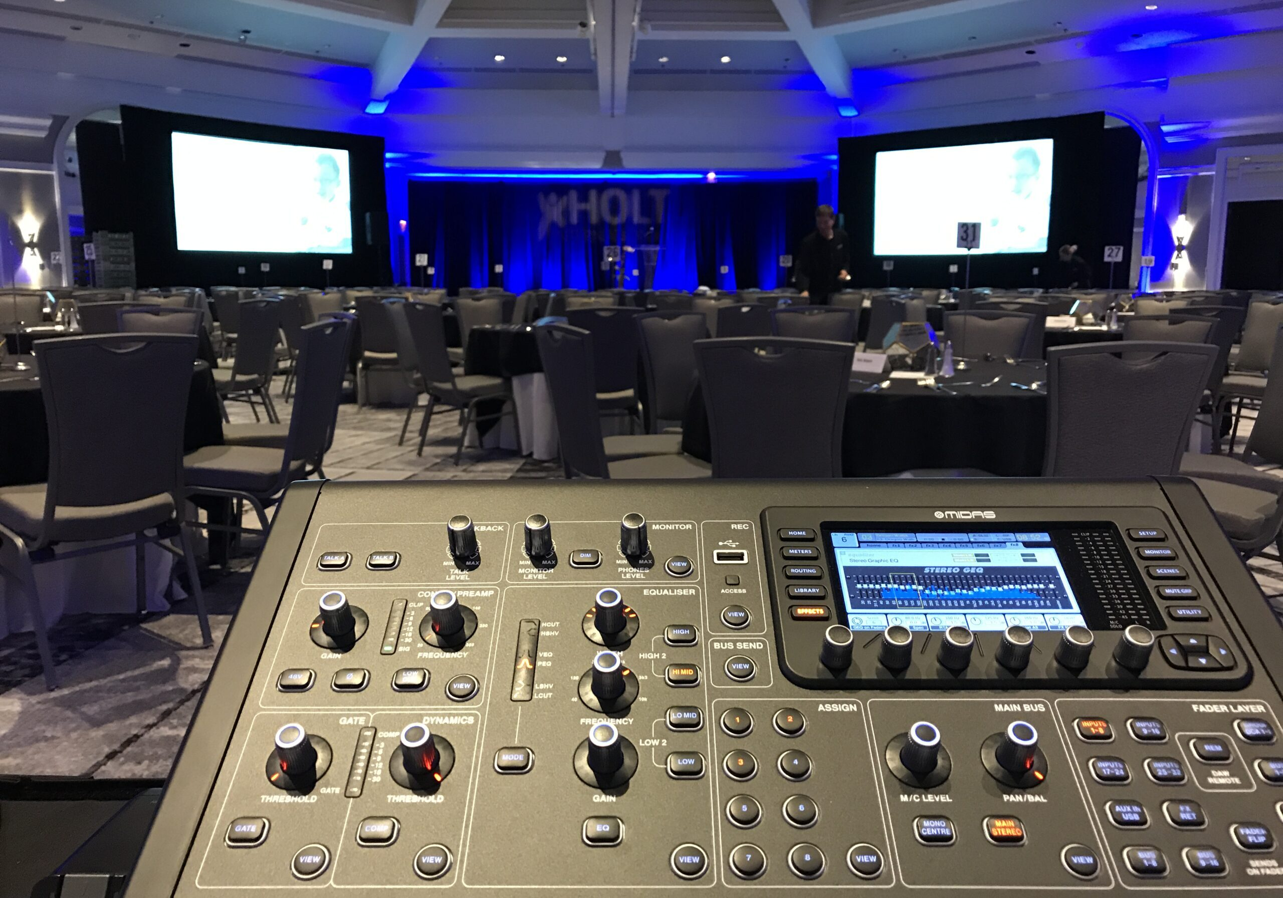 photo of a ballroom set up for an event with a mixing console in front and two large screens across the room