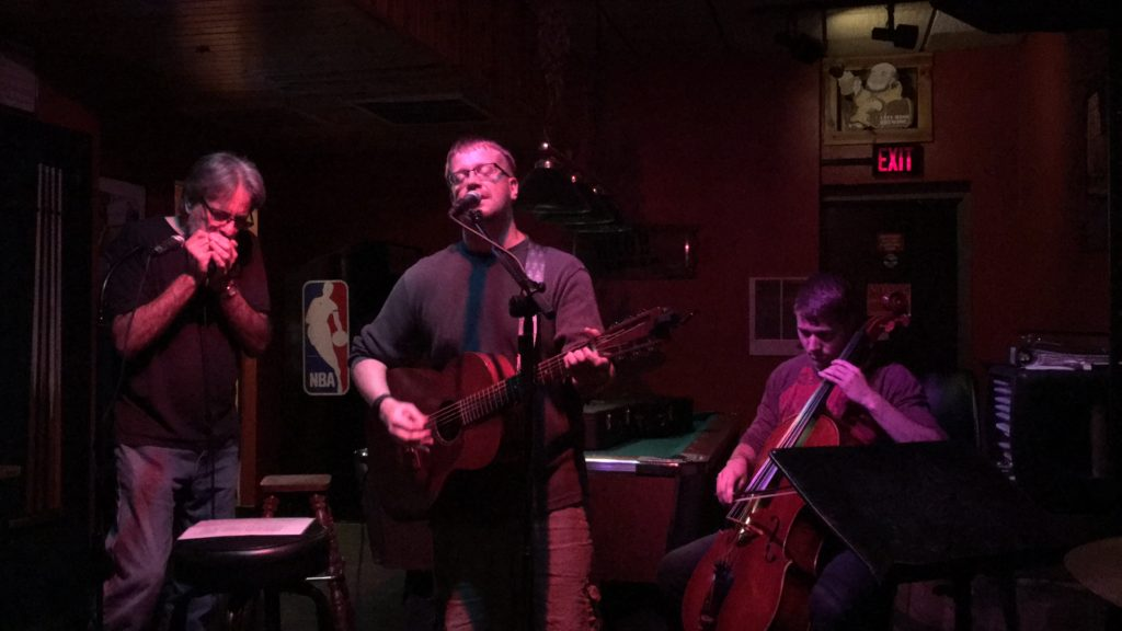 Jim Carlson performing with Duffy Duyfhuizen (harmonica) and Carter Clay (cello) at the Tomahawk Room, Chippewa Falls, WI