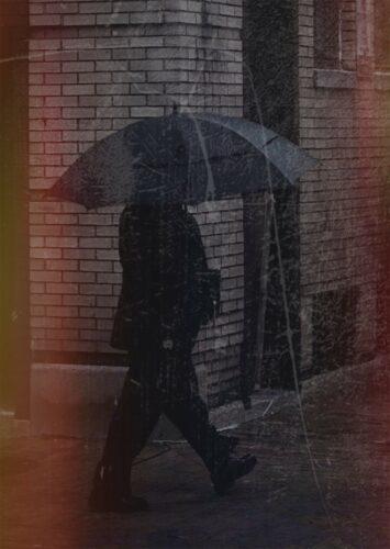 Man in black suit walking with black umbrella