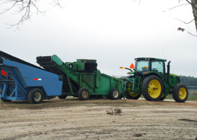 Tractor towing pecan harvesting equipment