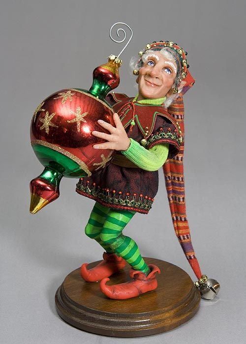Christmas Elf dressed in red elf shoes, green striped socks and a long red hat holding a Christmas ornament. fairiehollow