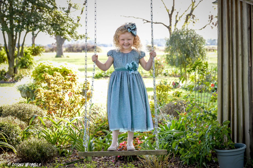AnnaLane is wearing the Winter Sparkle dress, style 9158TL, available in size 3M-6X.
