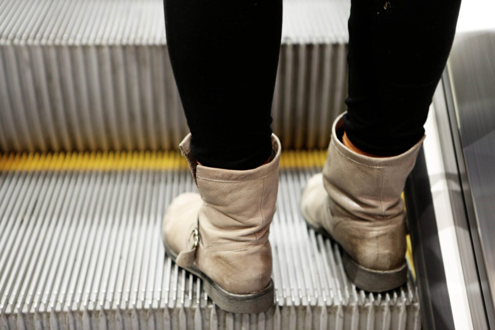 Legs in black leggings and boots on escalator