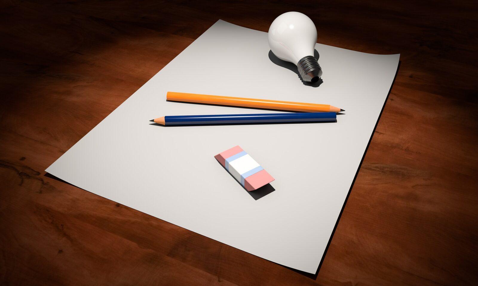 pink eraser, pencils and lightbulb on paper