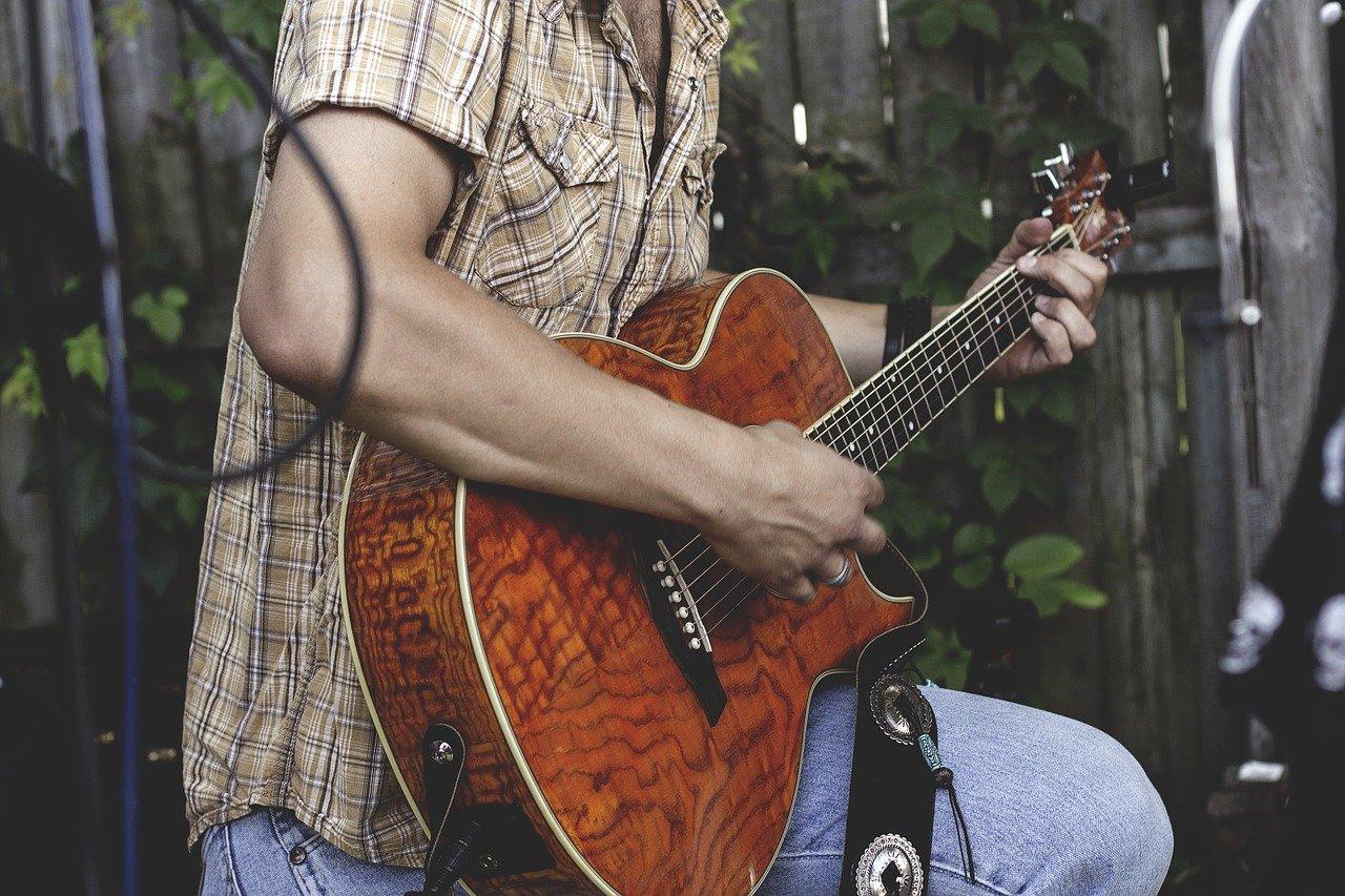 close up of man strumming guitar