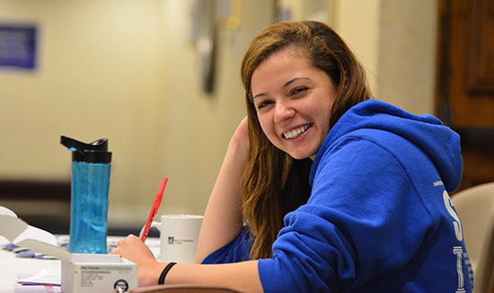 teen studying and smiling at camera