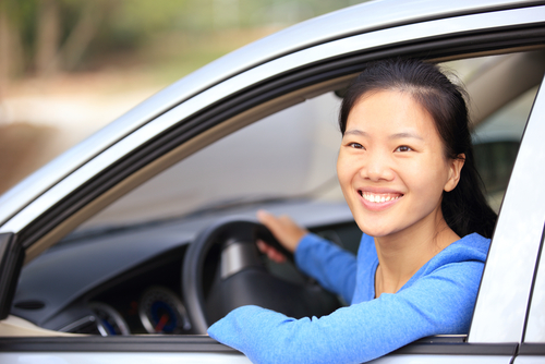 asian woman leaning out of car window smiling