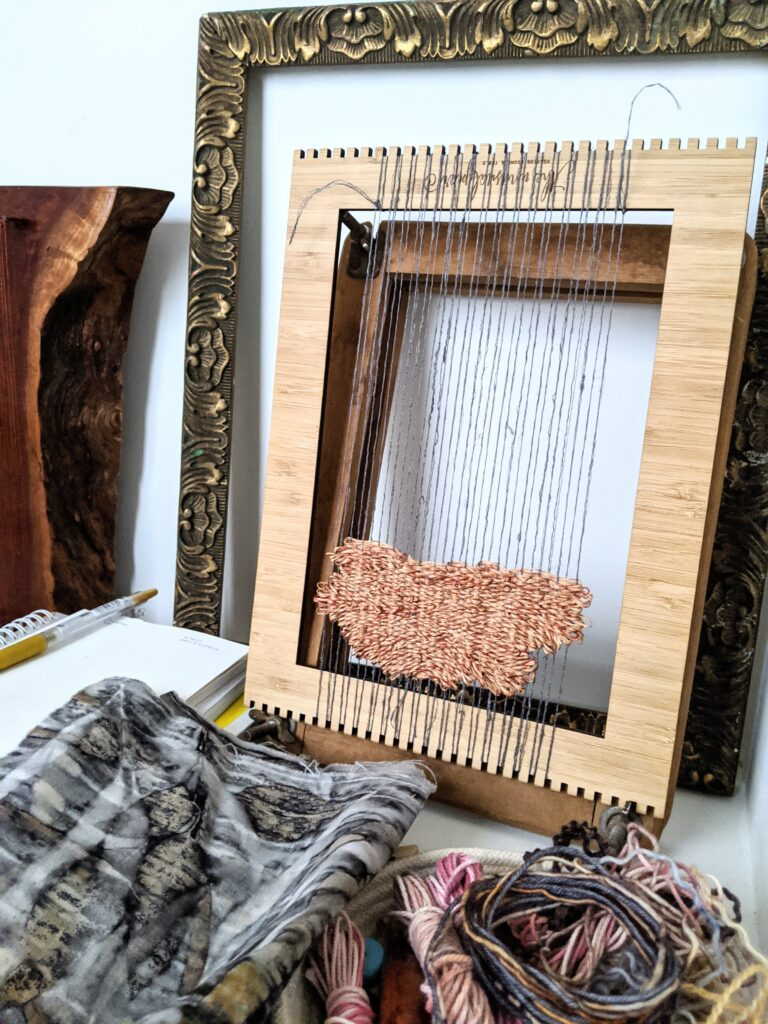 A photo of my first attempt to weave a project that failed. This picture shows weaving on a lap loom.