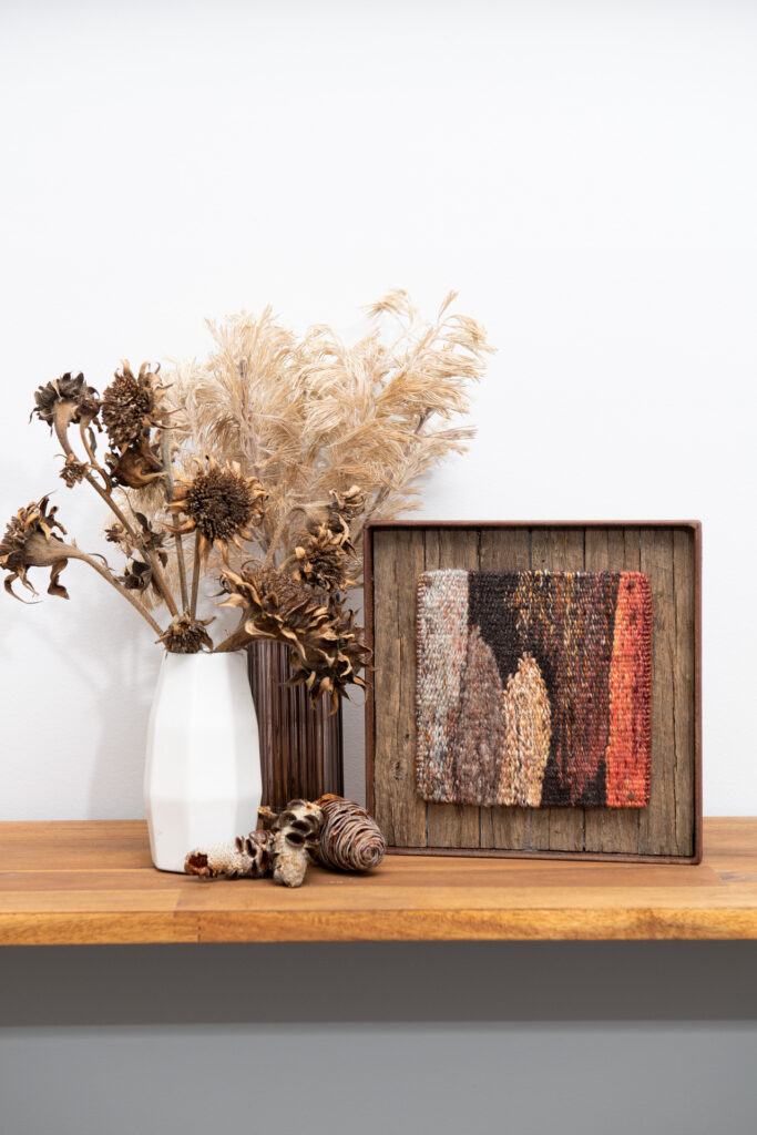 A small earthen coloured tapestry sits beside dried flower arrangements on a shelf