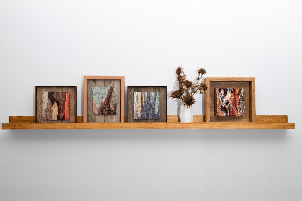Four framed tapestries side by side on a shelf. Each tapestry is a close up view of tree bark.