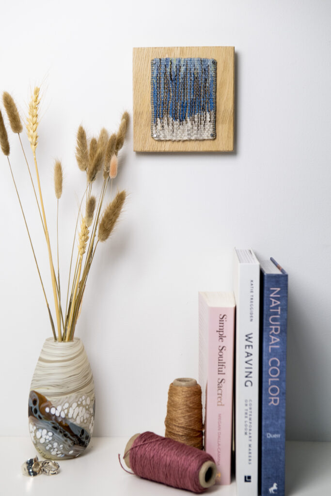 Winter tapestry hanging above books and vase