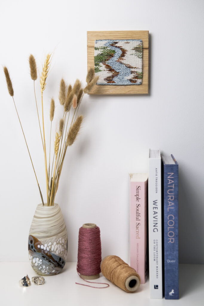 A winter tapestry hangs above books and a vase