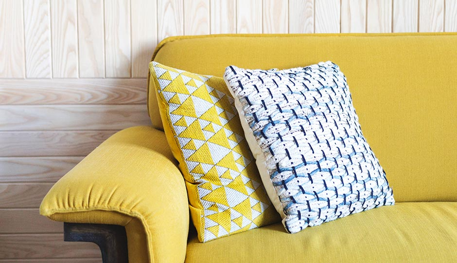 Yellow sofa with throw pillows