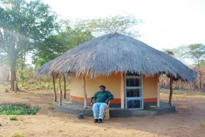 Mwizenge Tembo in front of his village hut.