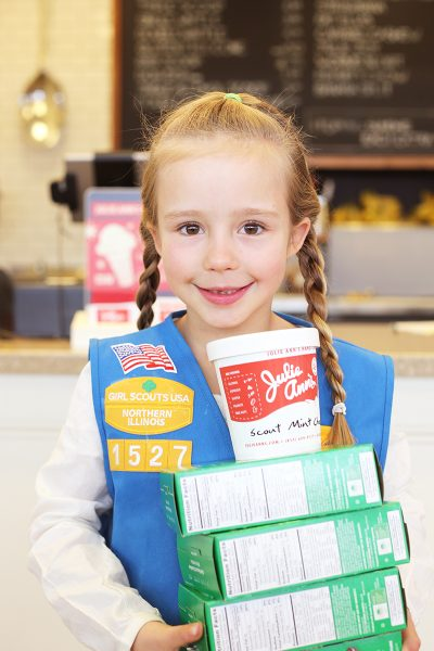 A photo of a Girl Scout with boxes of cookies and ice cream flavor made with the cookies