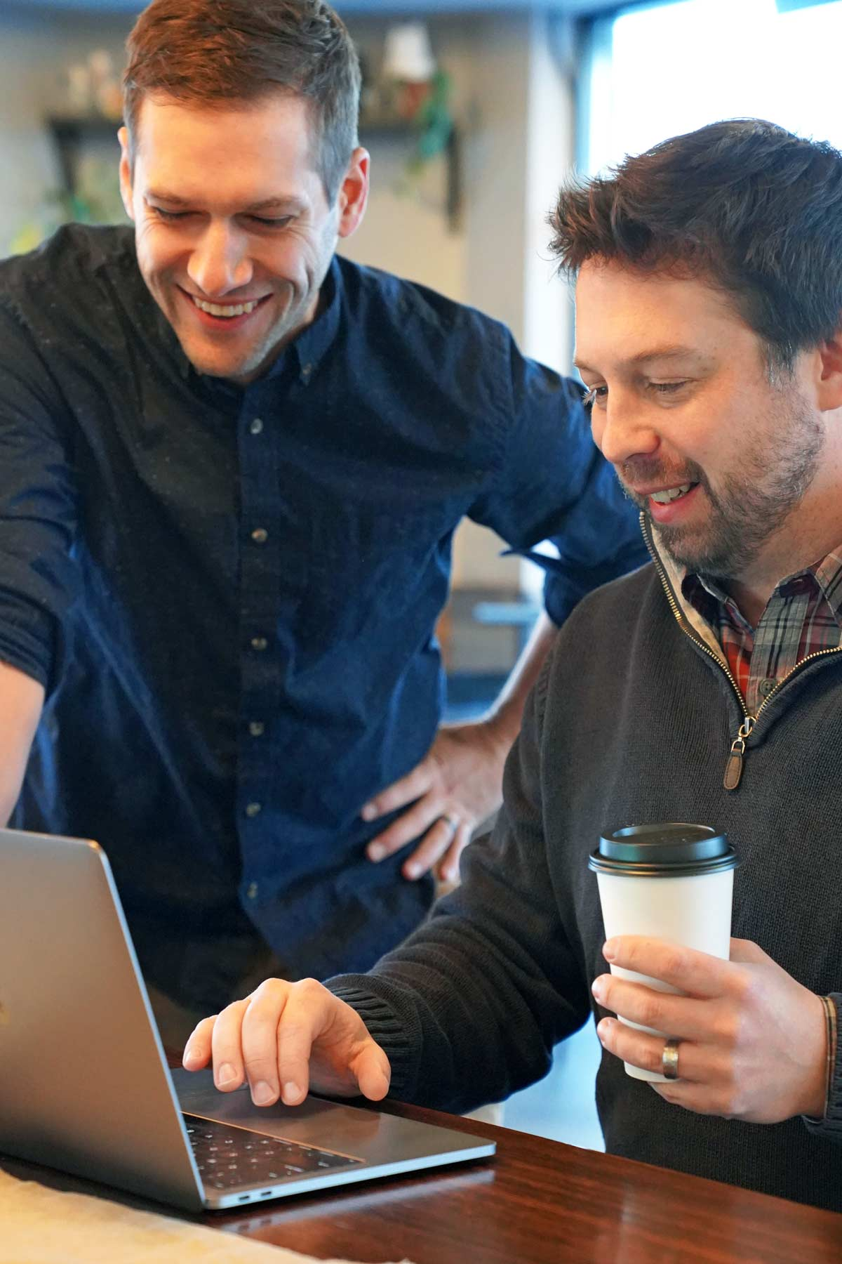 A photo of John Wisniewski and Matt Mallory working on a project and drinking coffee from Daily Projects Cafe