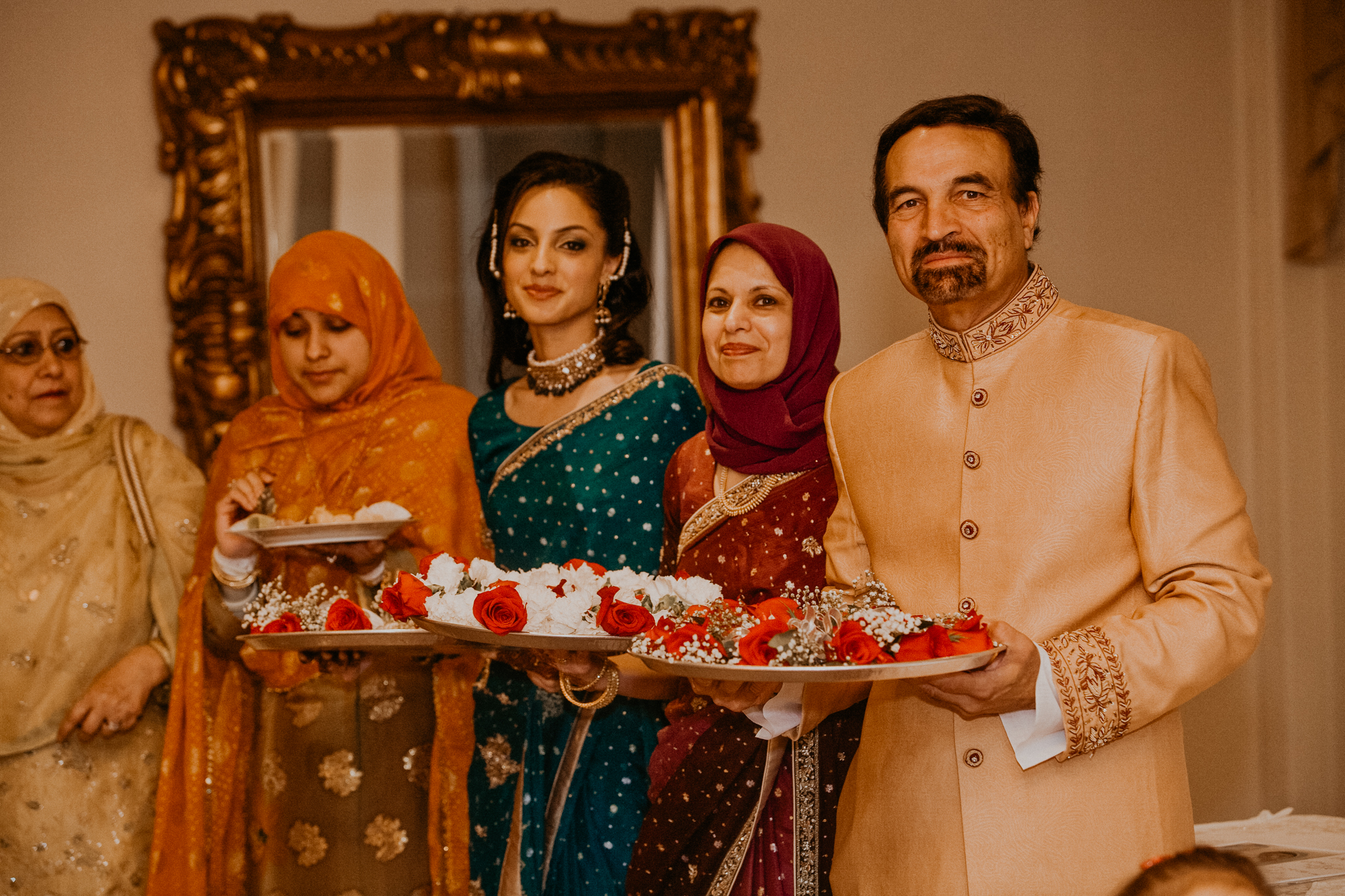 Family of bride wait to greet groom at Indian wedding