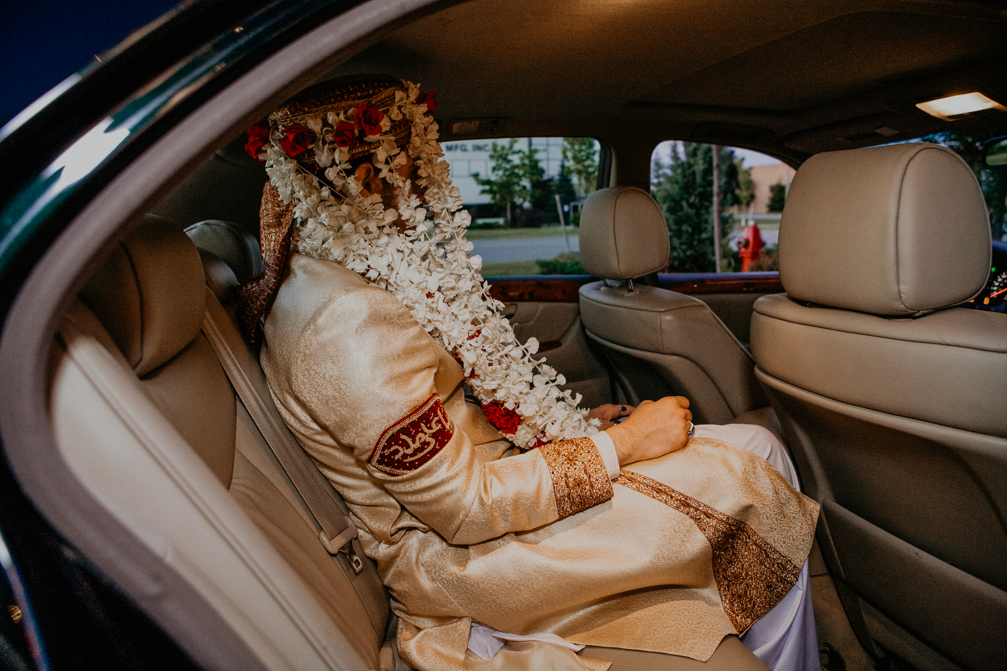 Indian groom in floral veil sits in car