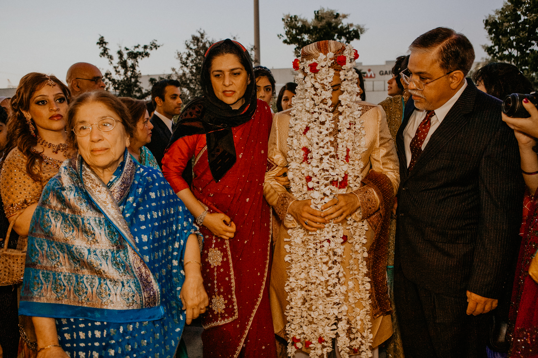 Indian groom in flower veil being led to ceremony by family