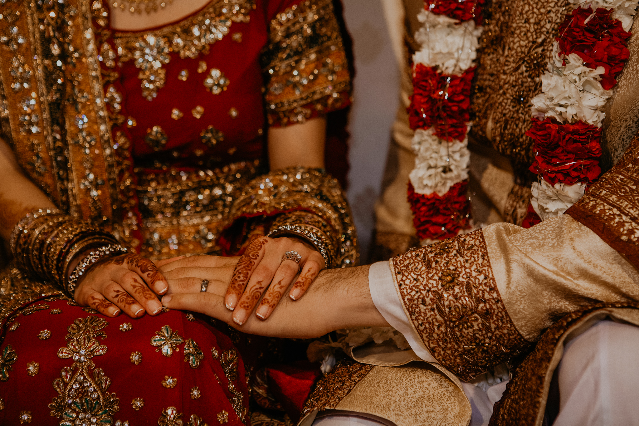 Close up of rings and bride and groom hands Indian wedding ceremony