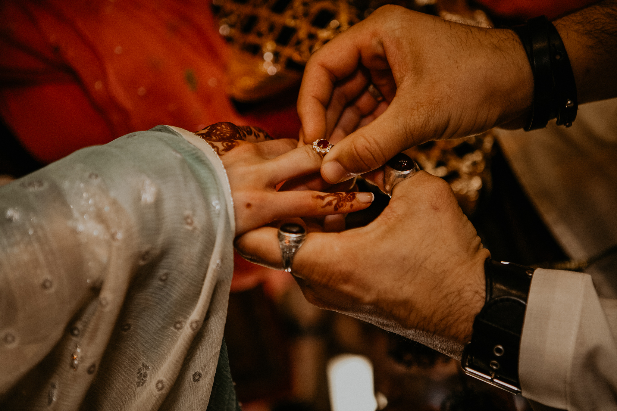Close up of groom placing ring on bride's finger at Nikah ceremony