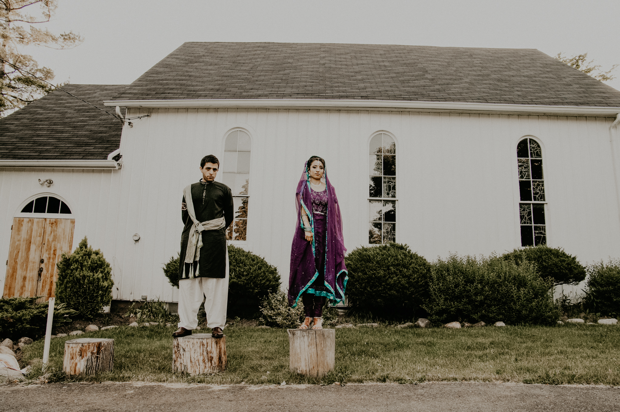 Bride and groom stand on logs outside temple at Indian wedding ceremony