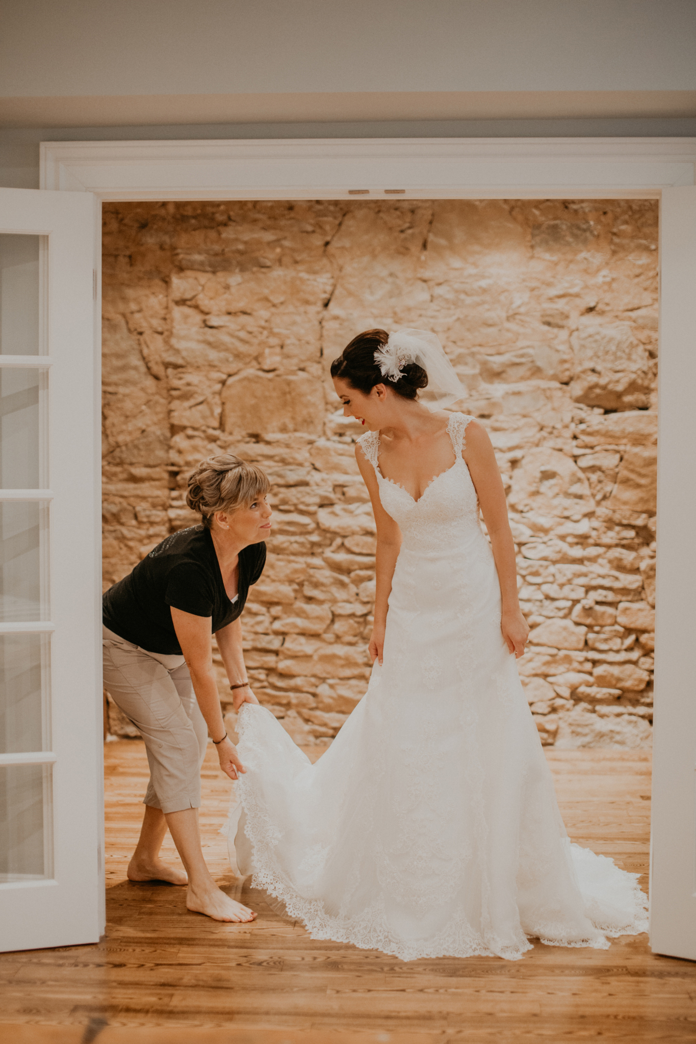 Mother of bride helps bride put on wedding dress