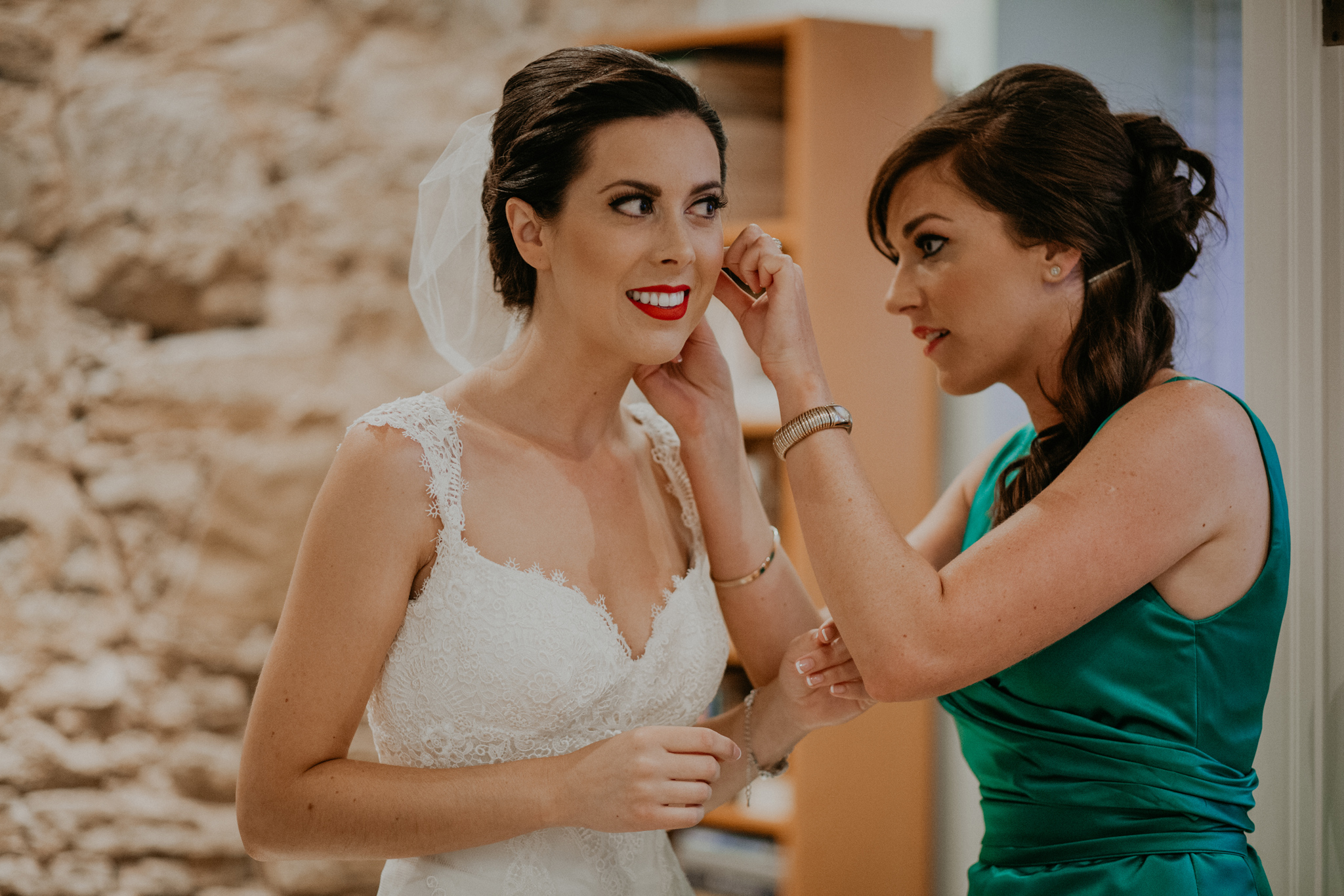 Bridesmaid helps bride put on earrings