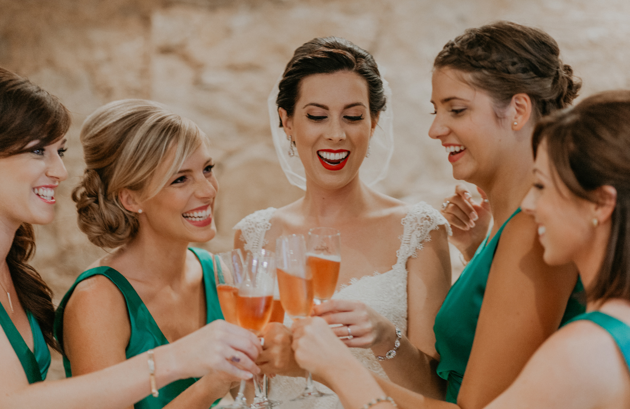 Bride and bridesmaids smile during champagne toast documentary wedding photograph