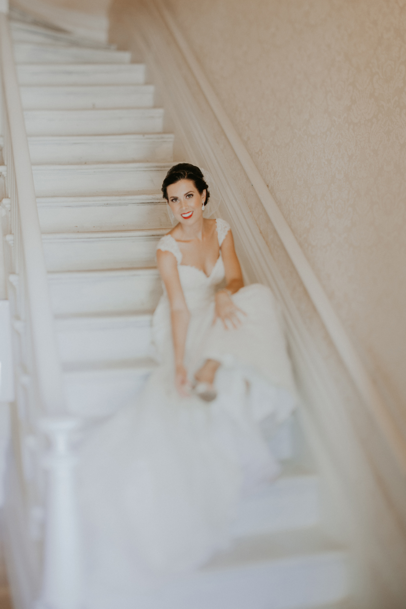 Portrait of bride on stairs putting on shoes