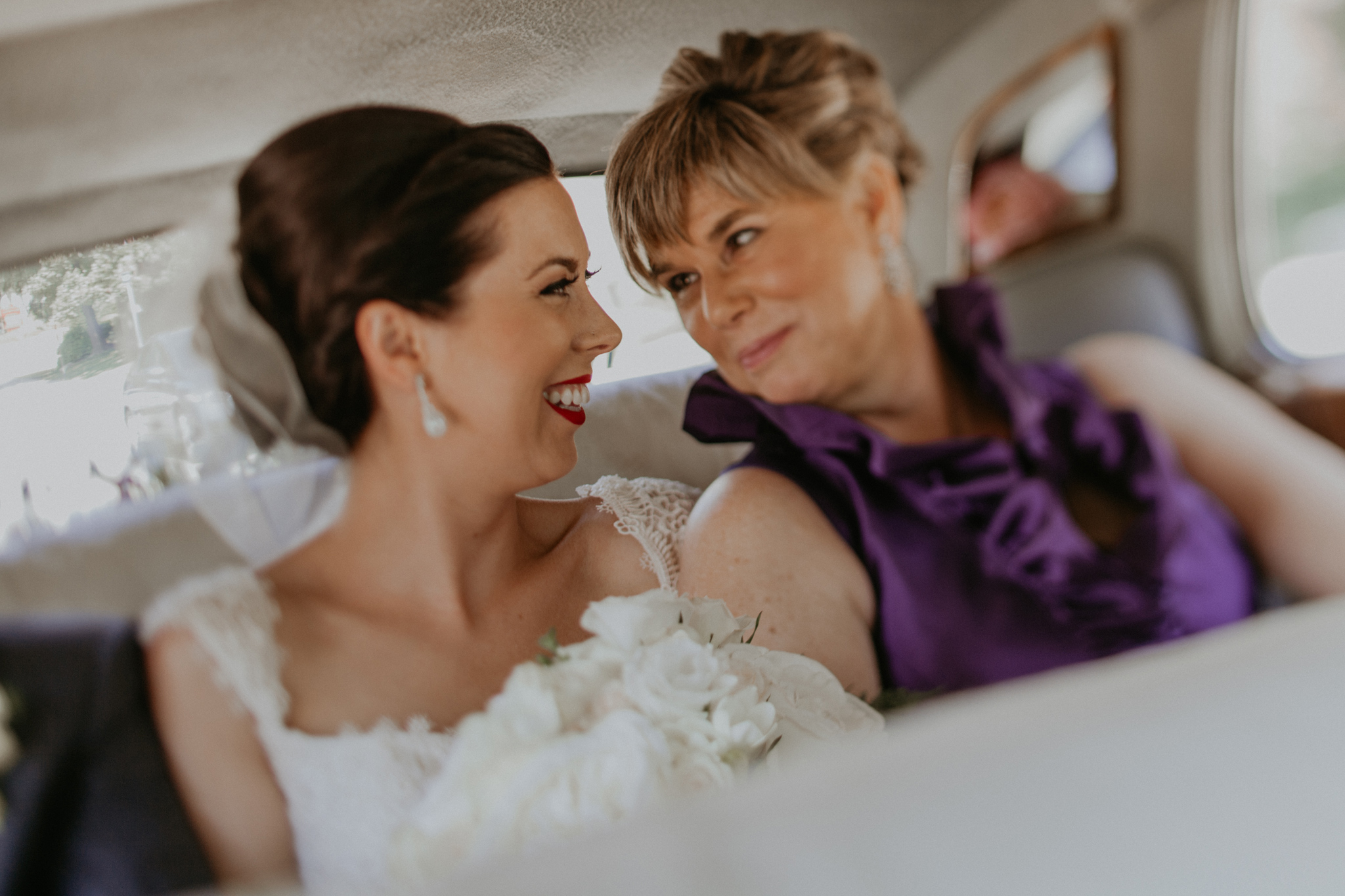 Bride and mother of bride smile at each other