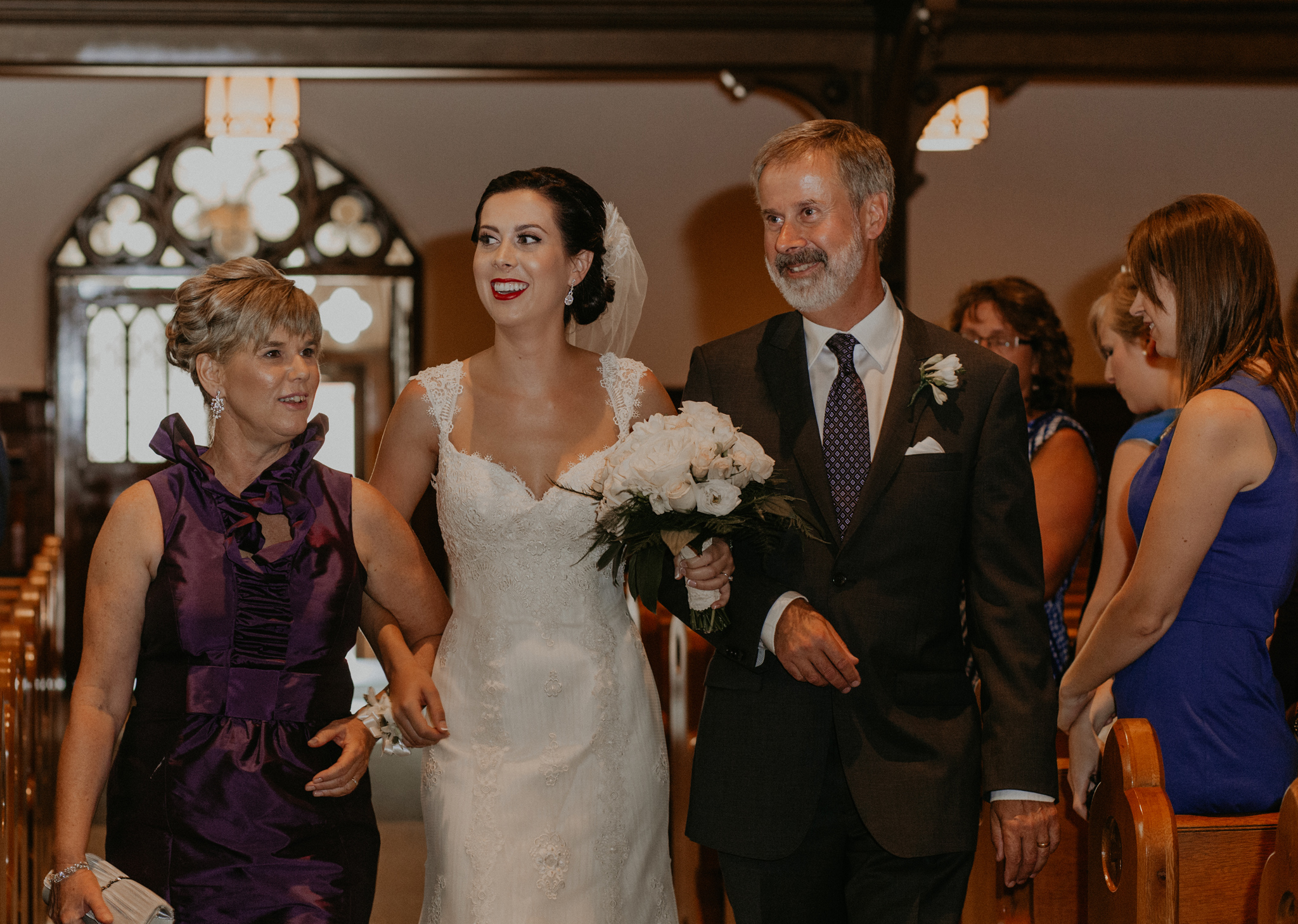 Bride walks up aisle with mom and dad during church ceremony