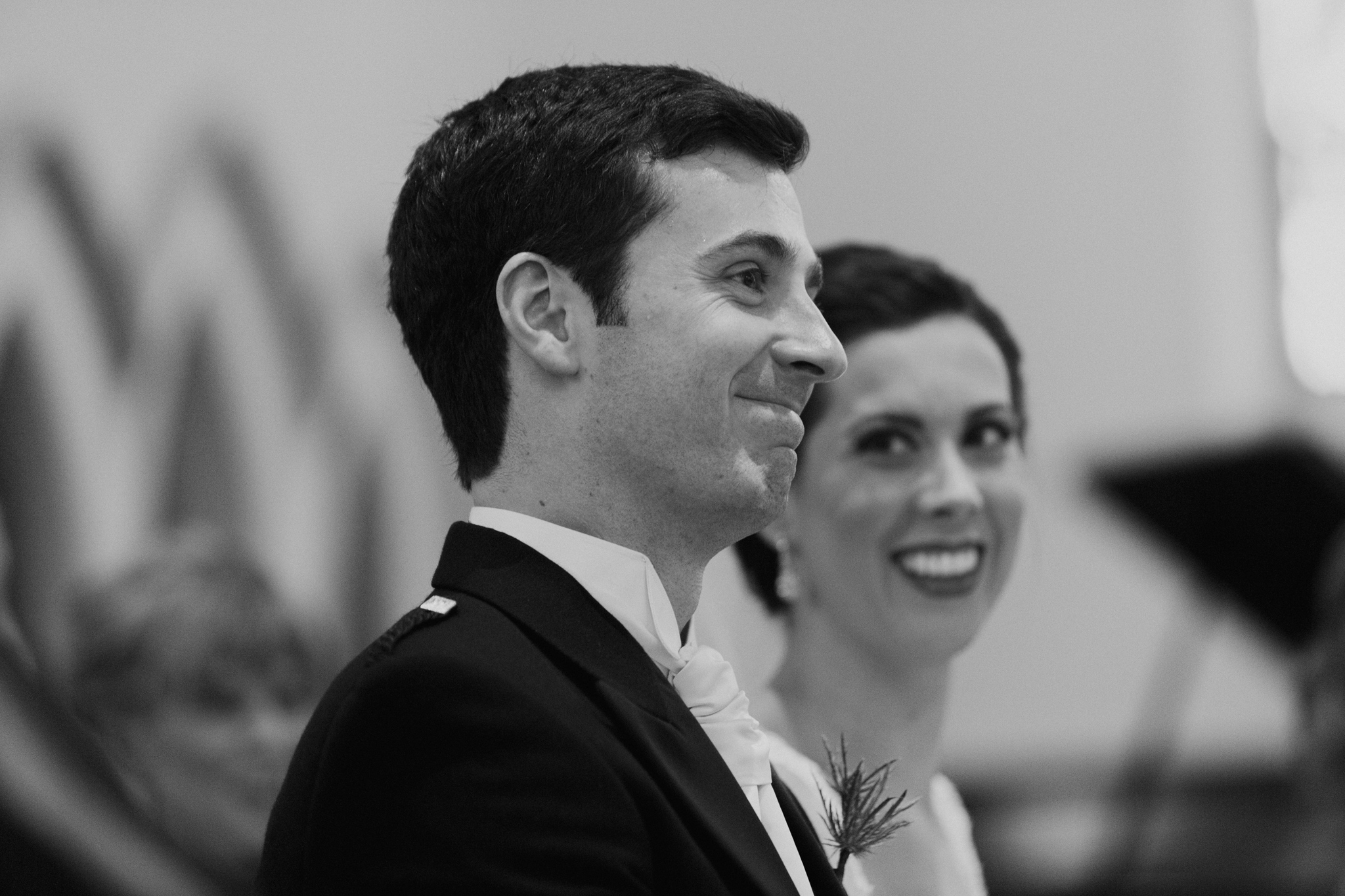 Bride smiles at groom while groom smiles and looks forward in church ceremony