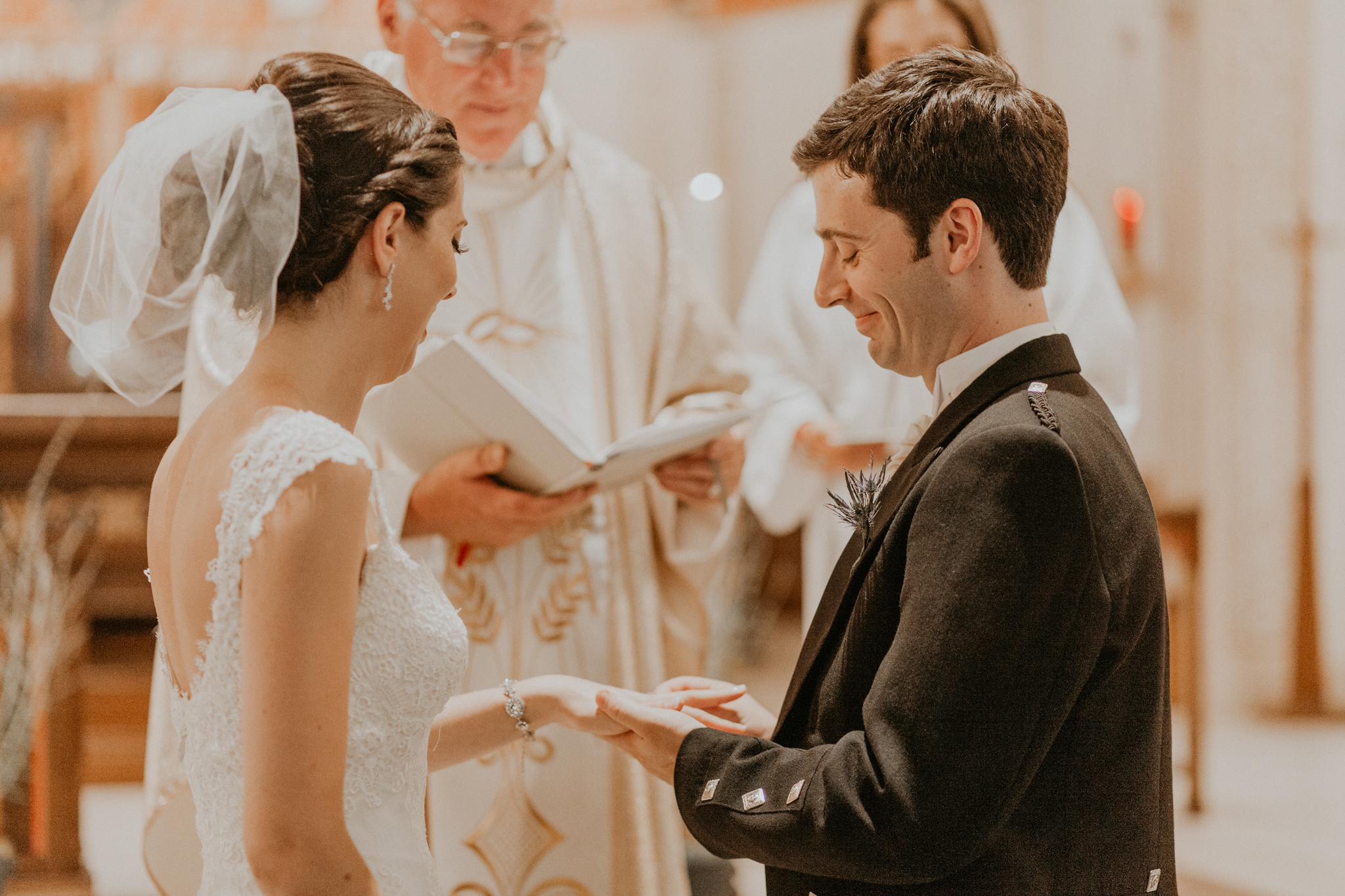 Groom smiling while placing ring on bride's finger