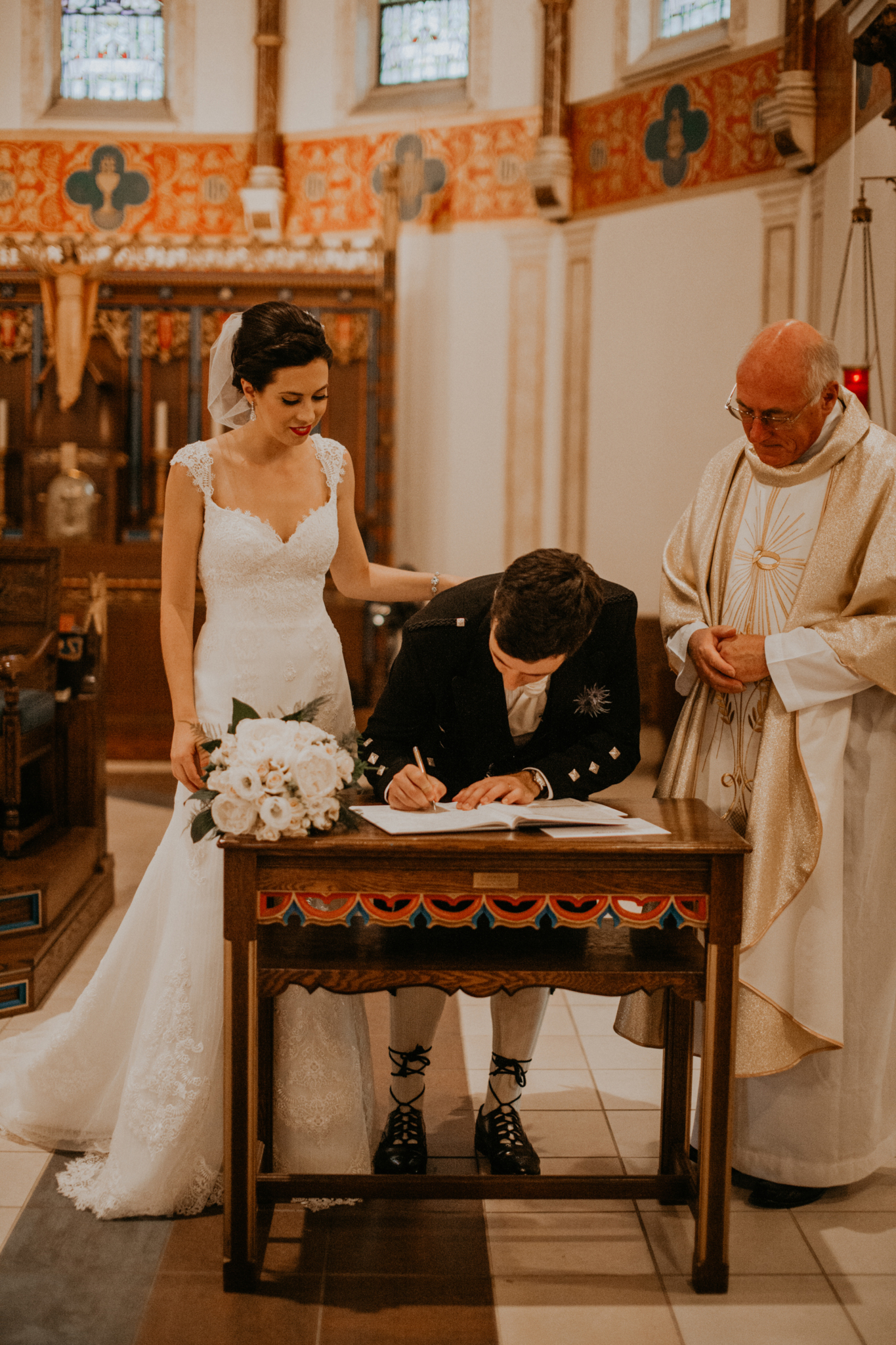 Bride and groom smiling while signing register in church Niagara Ontario wedding