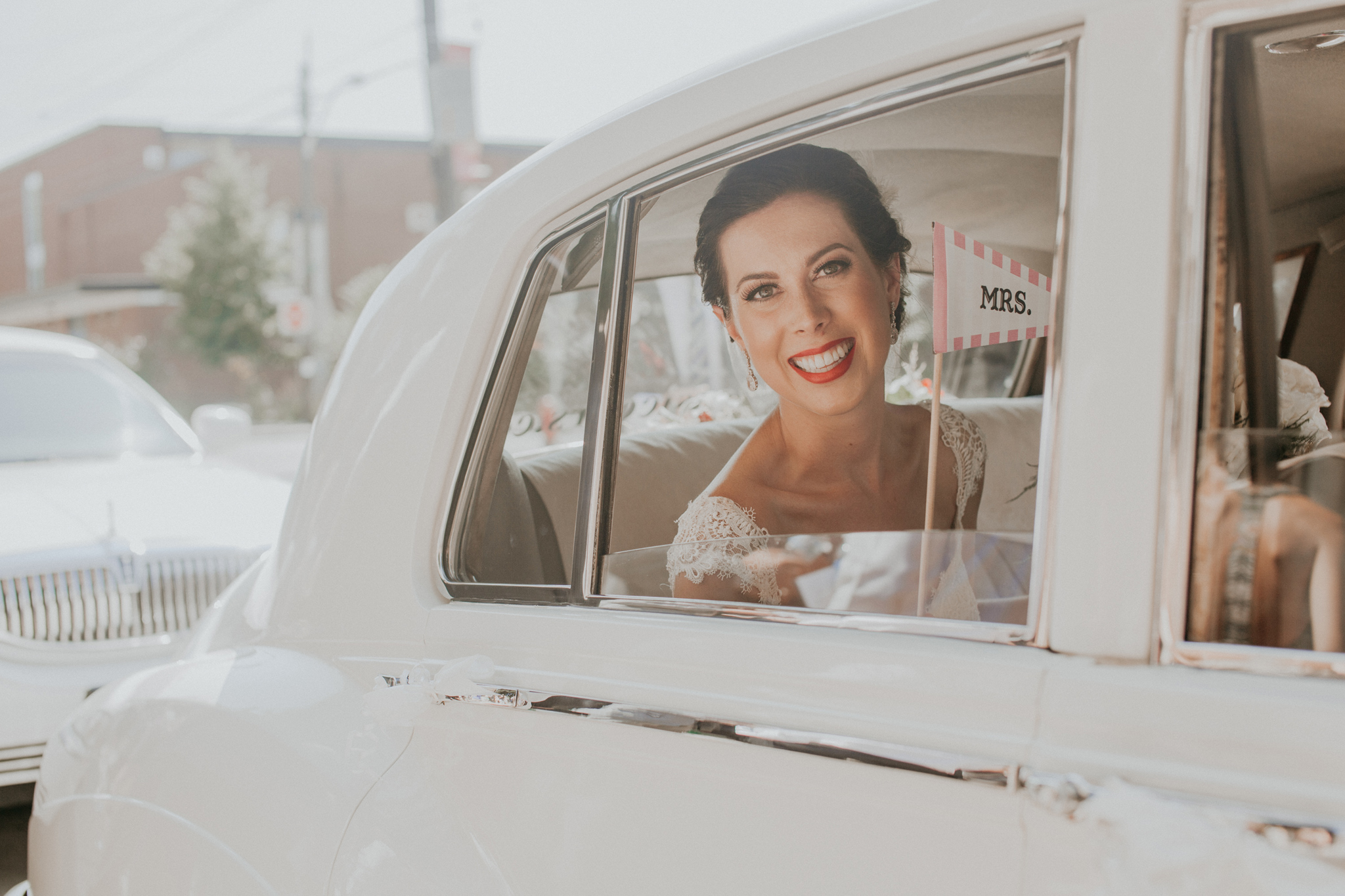 Happy bride smiling in car on wedding day