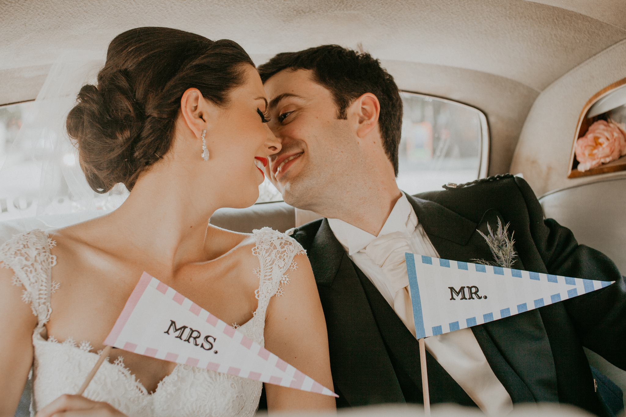 Couple of bride and groom kissing in car
