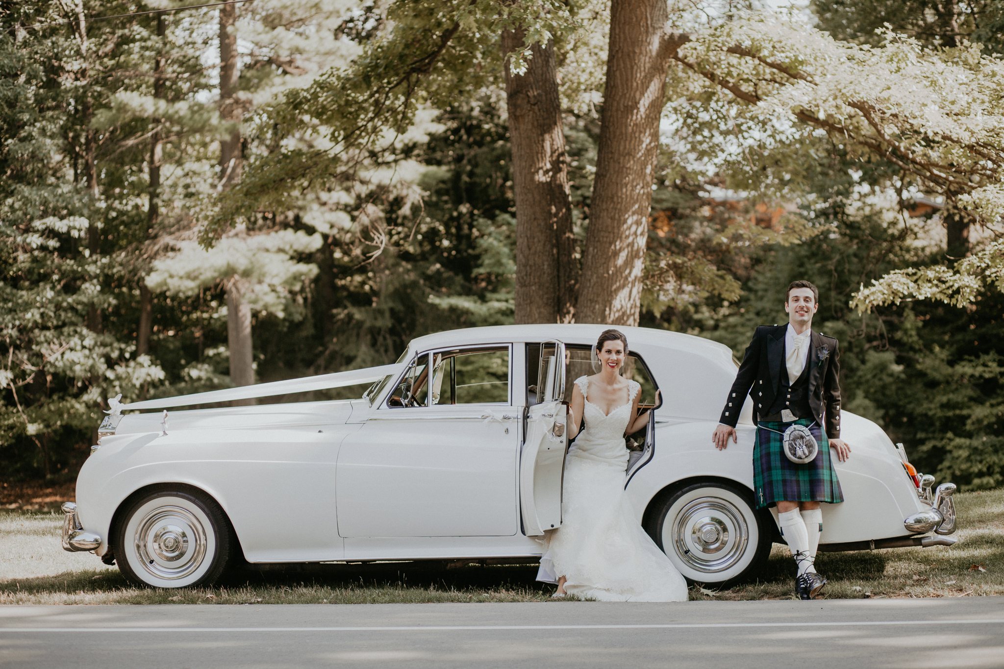 Portrait of bride and groom with Rolls Royce car