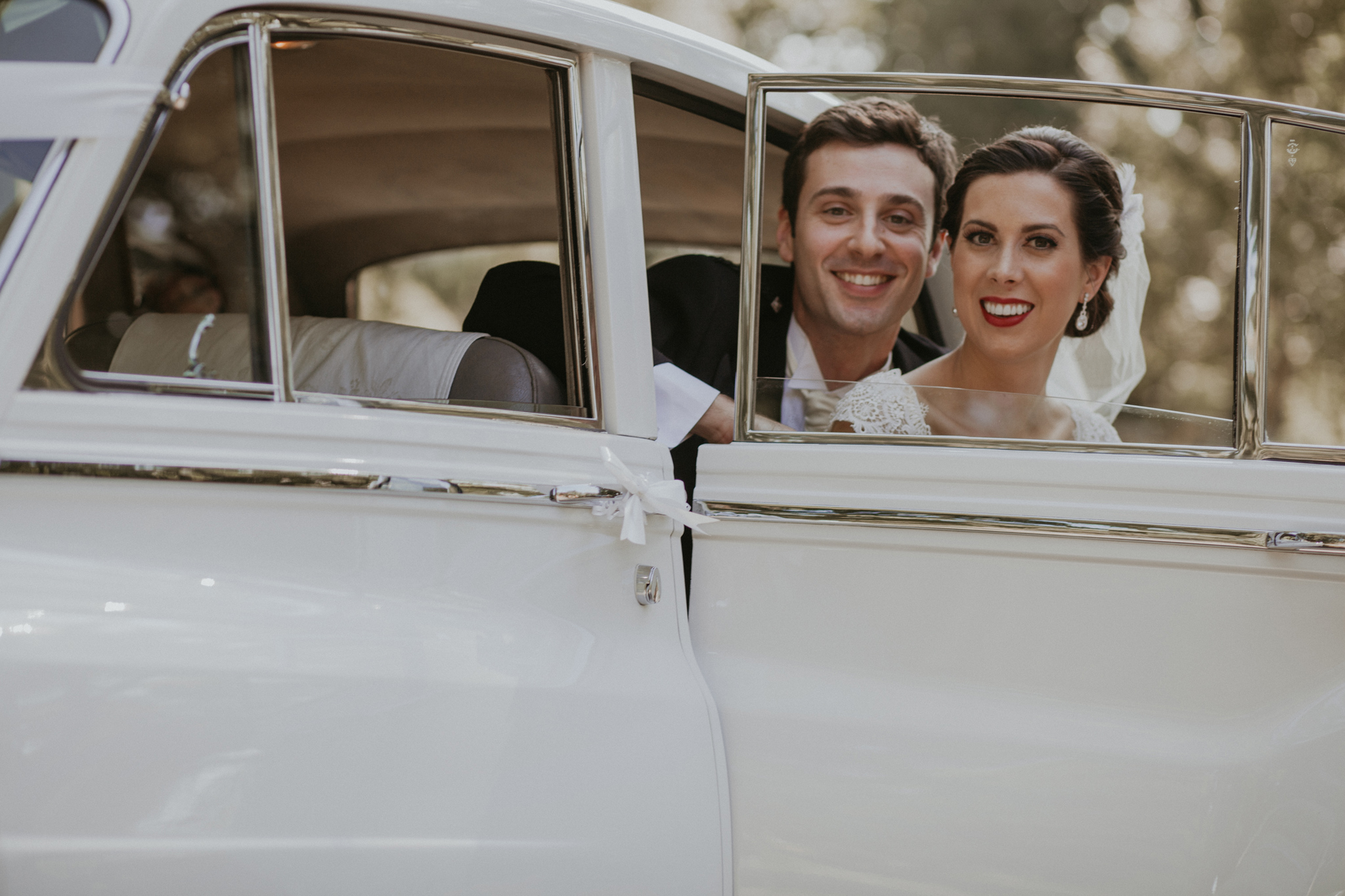 Portrait of bride and groom smiling in Rolls Royce car