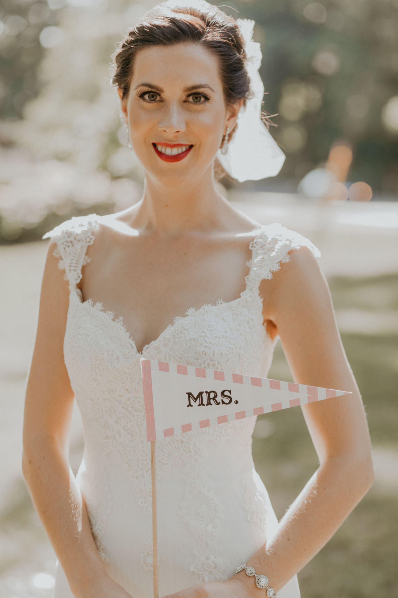 "Portrait of bride on wedding day holding ""Mrs"" flag"
