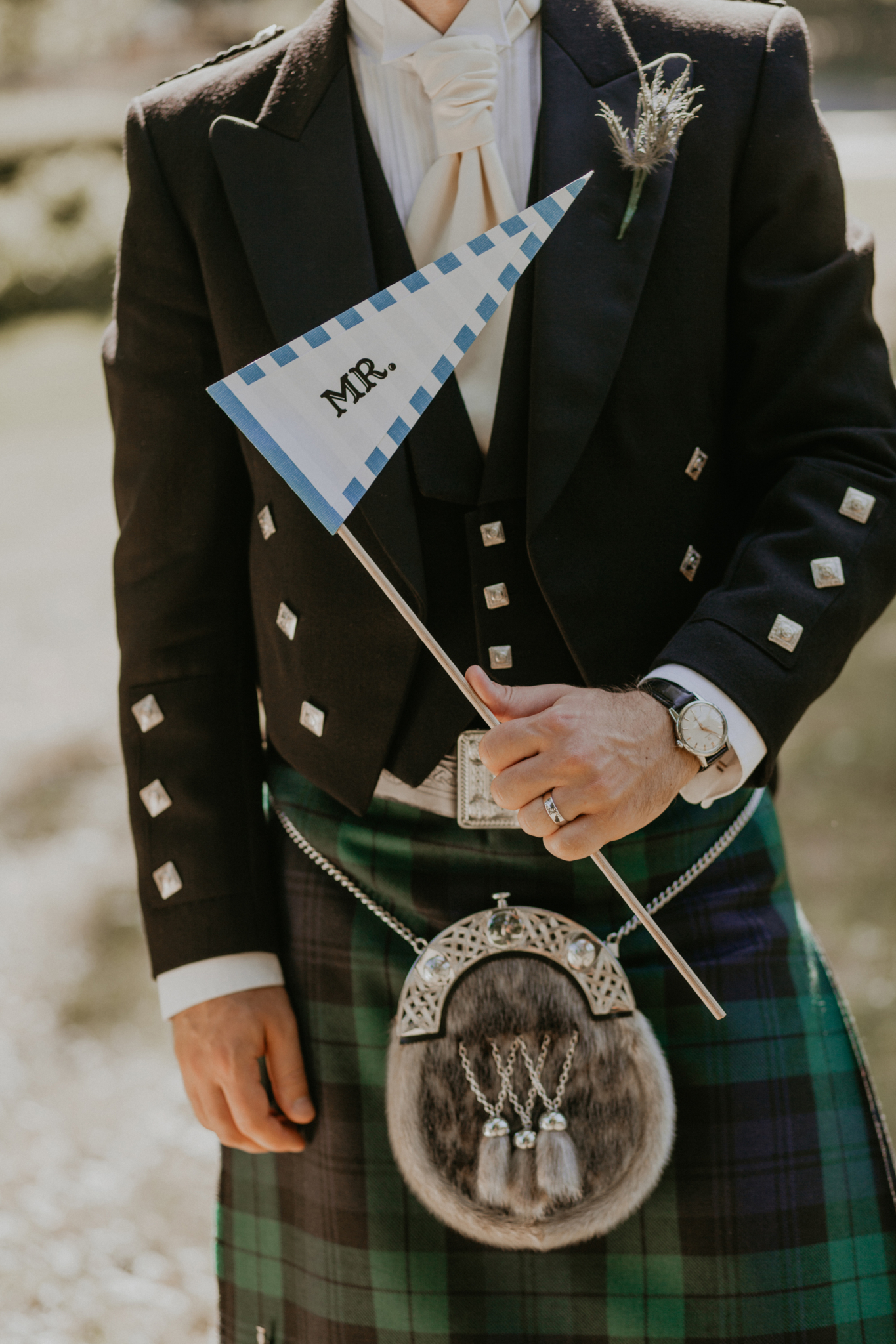 "Close up of groom on wedding day holding ""Mr."" flag"