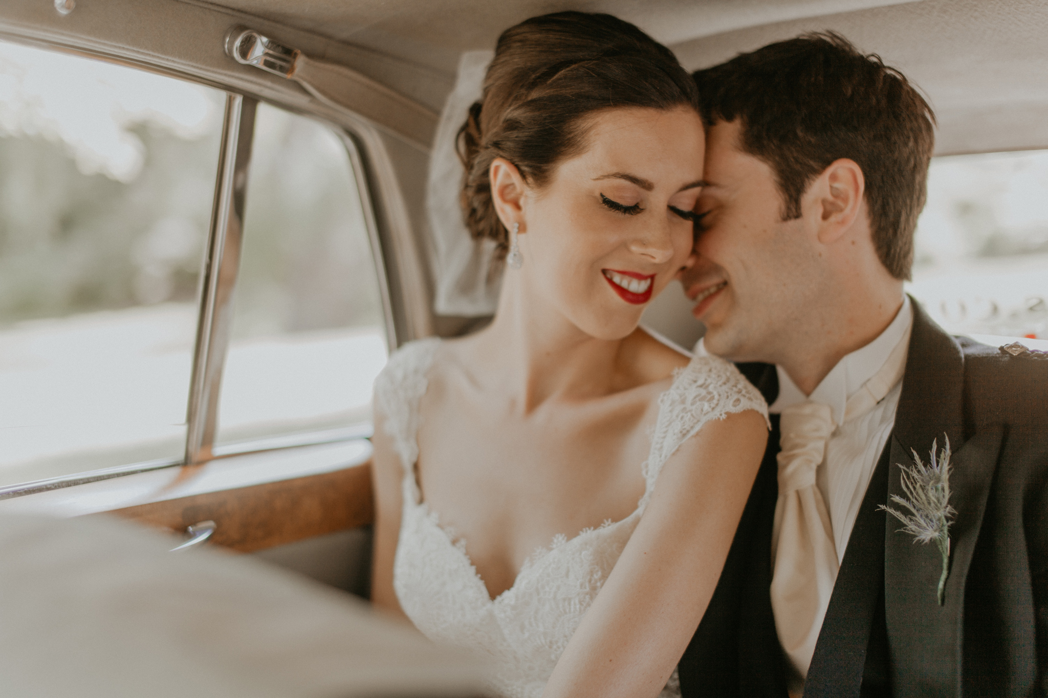 Bride and groom romantic photo in car on wedding day