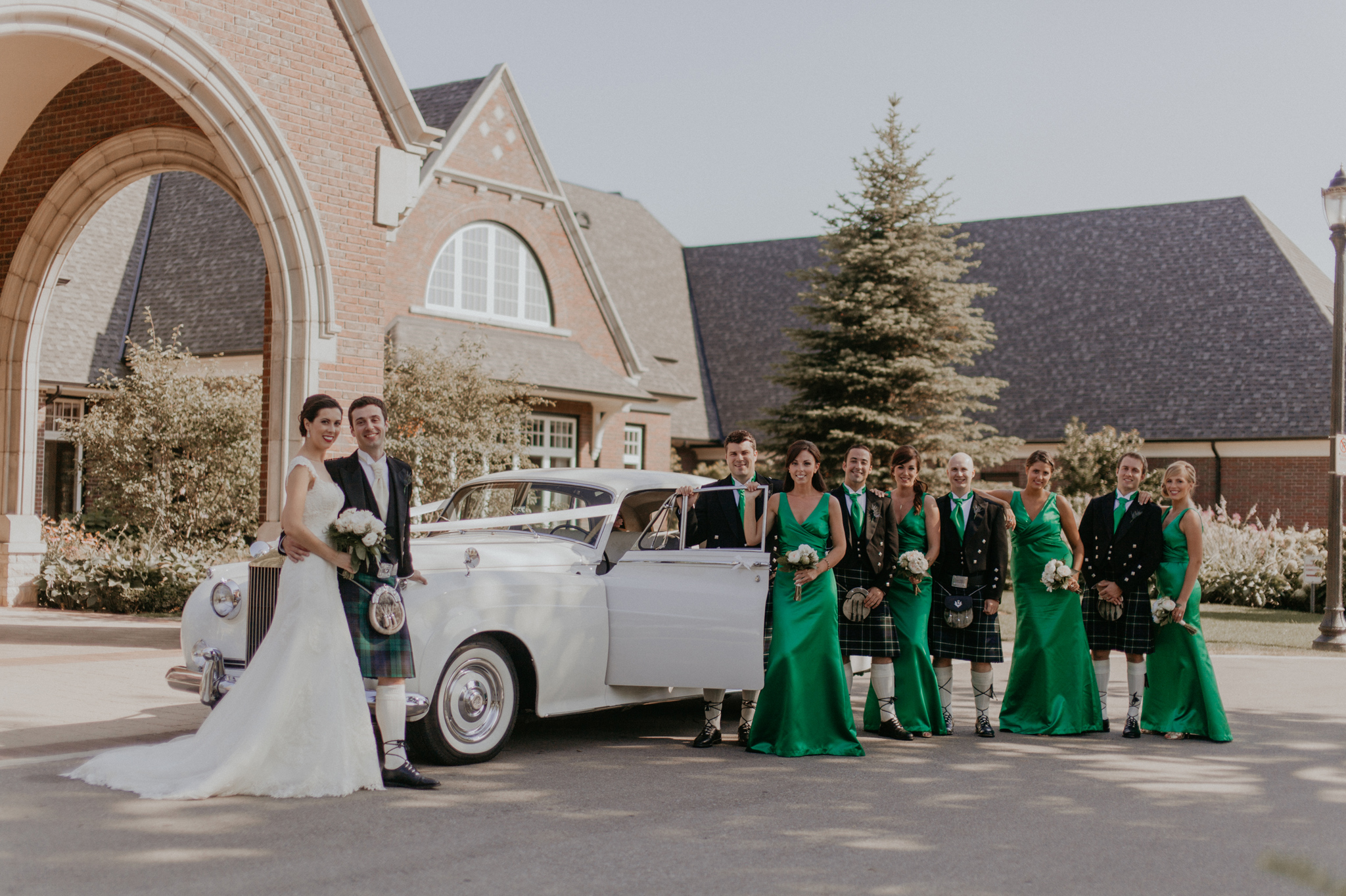 Wedding party pose in kilts and green bridesmaid's dresses with Rolls Royce