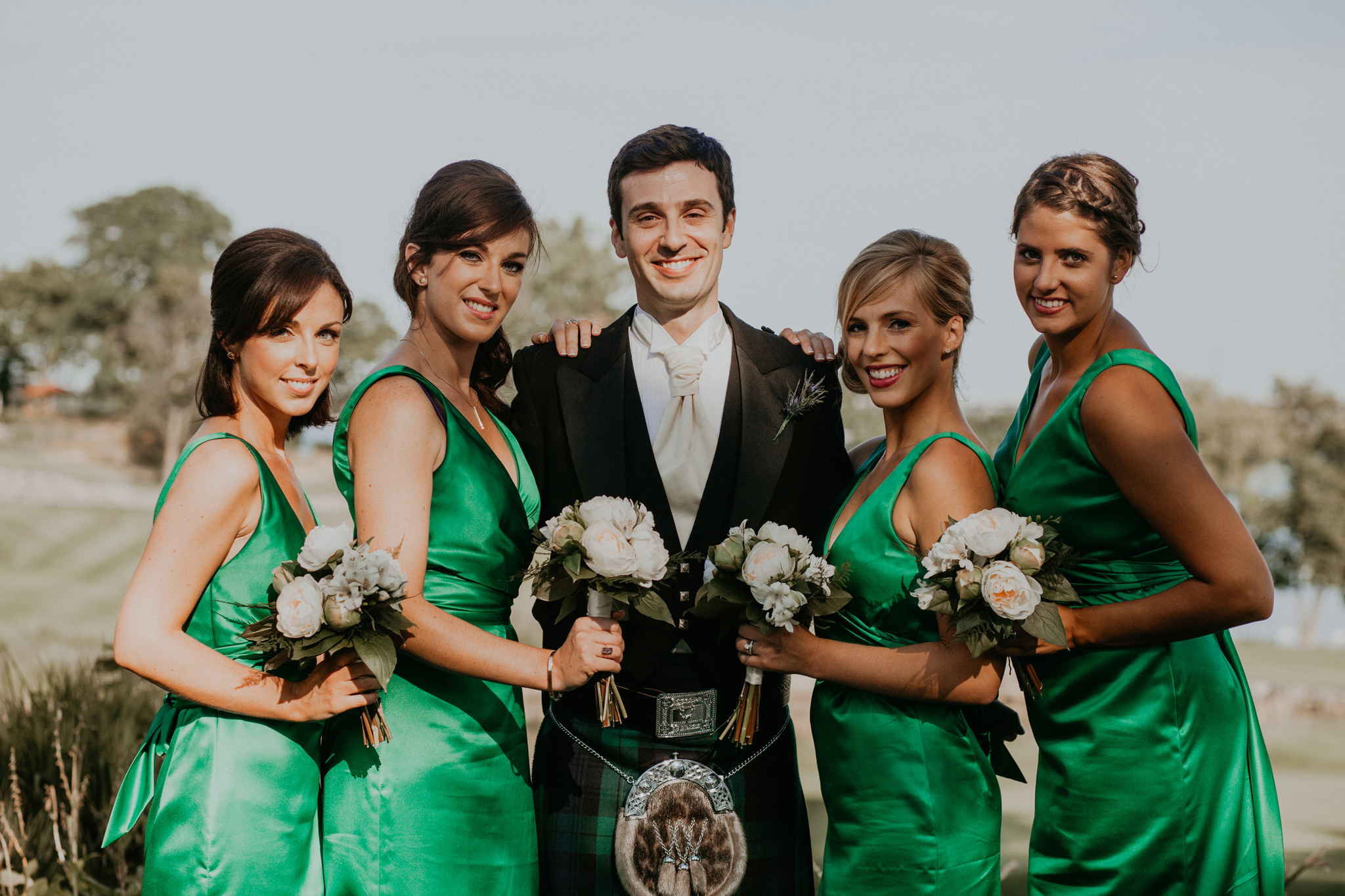 Bridesmaids pose with groom